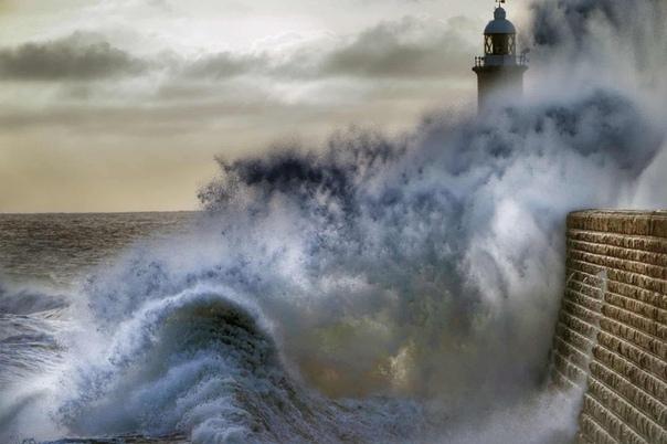 Волны разбиваются о пирс на северо-восточном побережье Великобритании