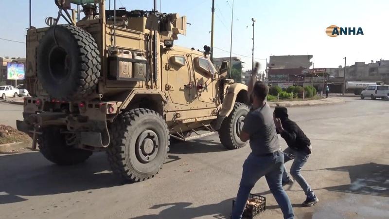 жители сирийского города Камышлы бросают камни и помидоры в колонну американских военных автомобилей, покидающих Сирию.